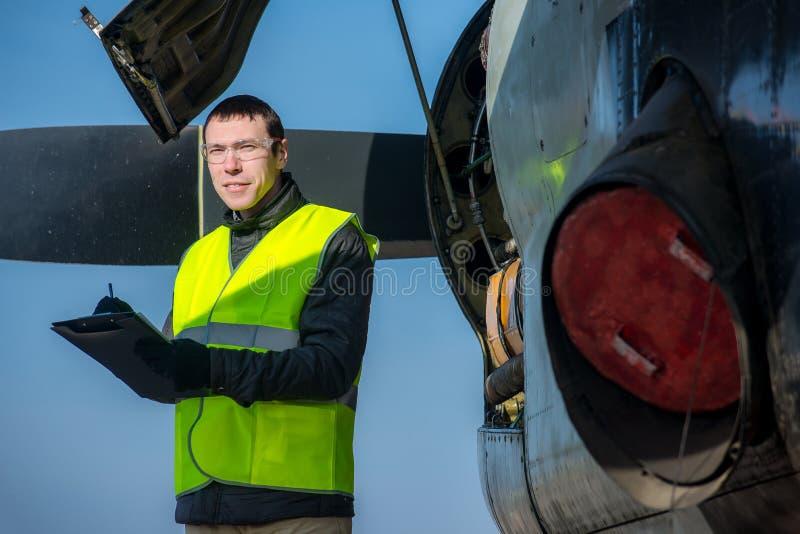 Meccanico che controlla airplane& x27; motore di s fotografia stock