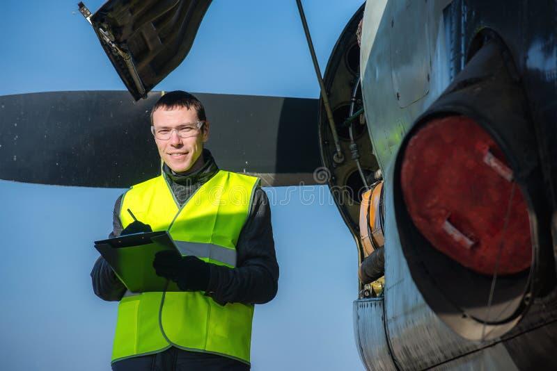 Meccanico che controlla airplane& x27; motore di s immagine stock