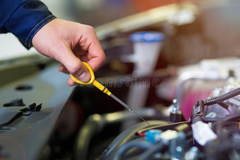 Meccanico che controlla l'olio per motori nell'officina riparazioni automatica immagini stock