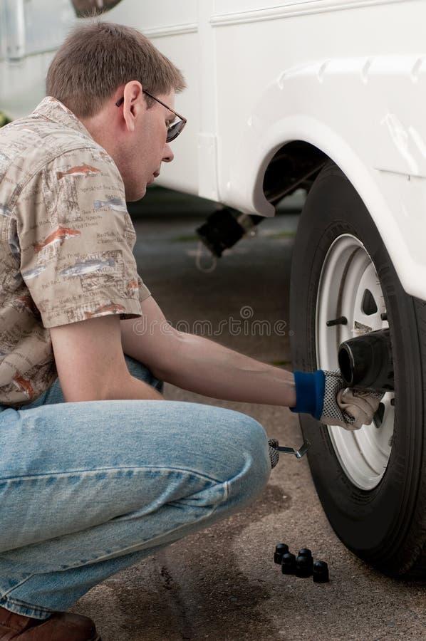 Meccanico che controlla le noci dell'aletta sulle rotelle del camion fotografie stock
