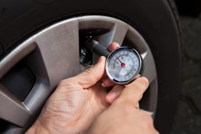 Meccanico che controlla pressione di gomma facendo uso del calibro fotografia stock libera da diritti
