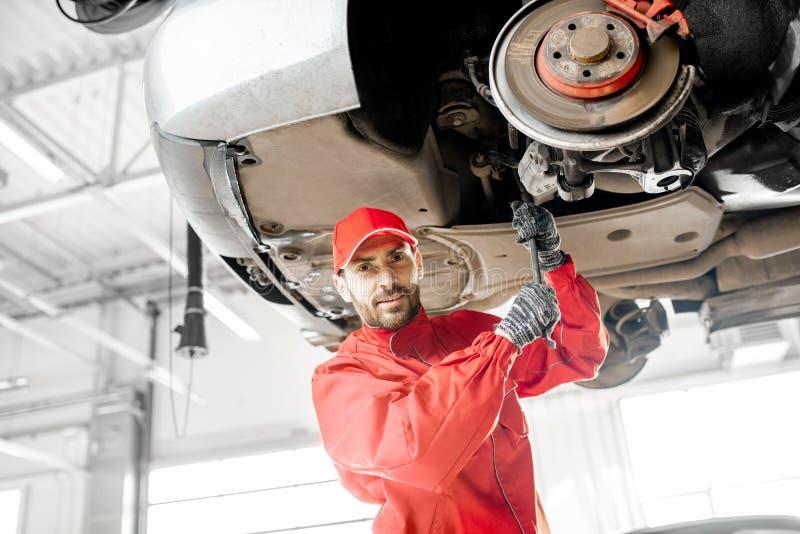 Meccanico che diagnostica automobile al servizio dell'automobile fotografie stock libere da diritti