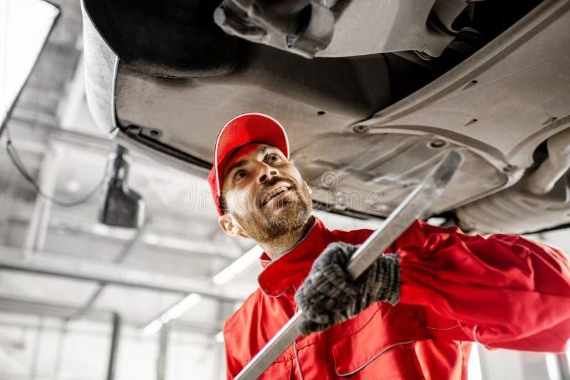 Meccanico che diagnostica automobile al servizio dell'automobile fotografie stock