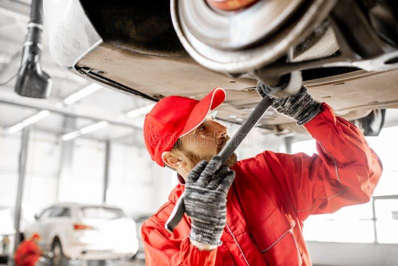 Meccanico che diagnostica automobile al servizio dell'automobile fotografia stock