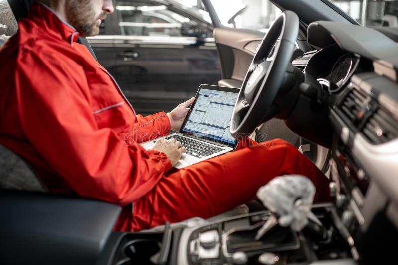 Meccanico che diagnostica automobile con il computer immagine stock libera da diritti