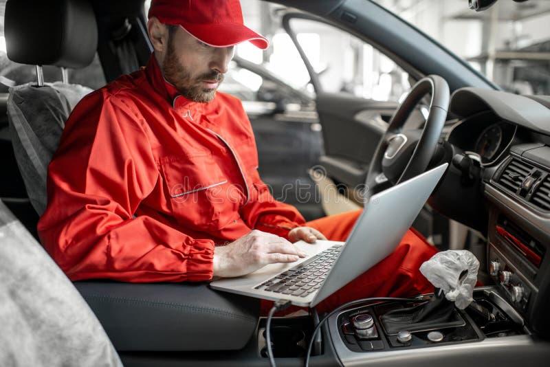 Meccanico che diagnostica automobile con il computer fotografia stock libera da diritti