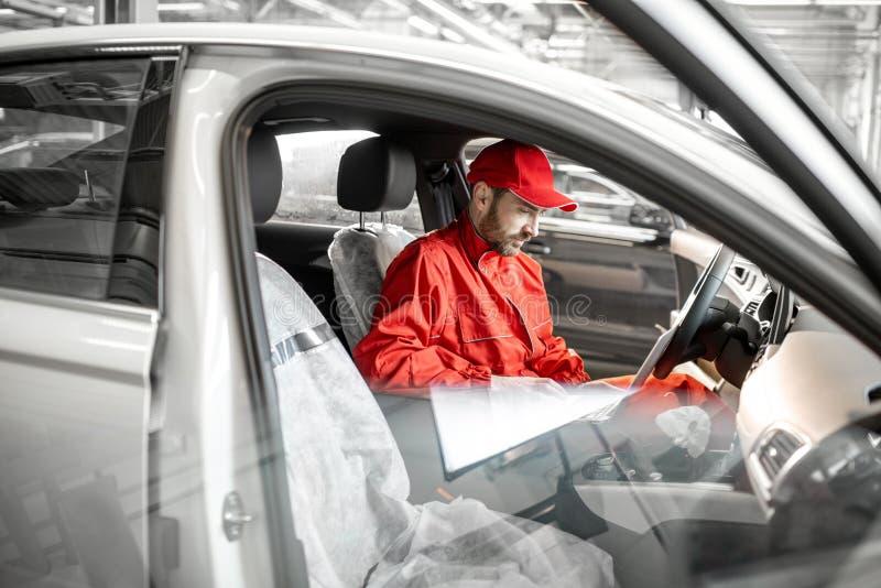 Meccanico che diagnostica automobile con il computer immagini stock