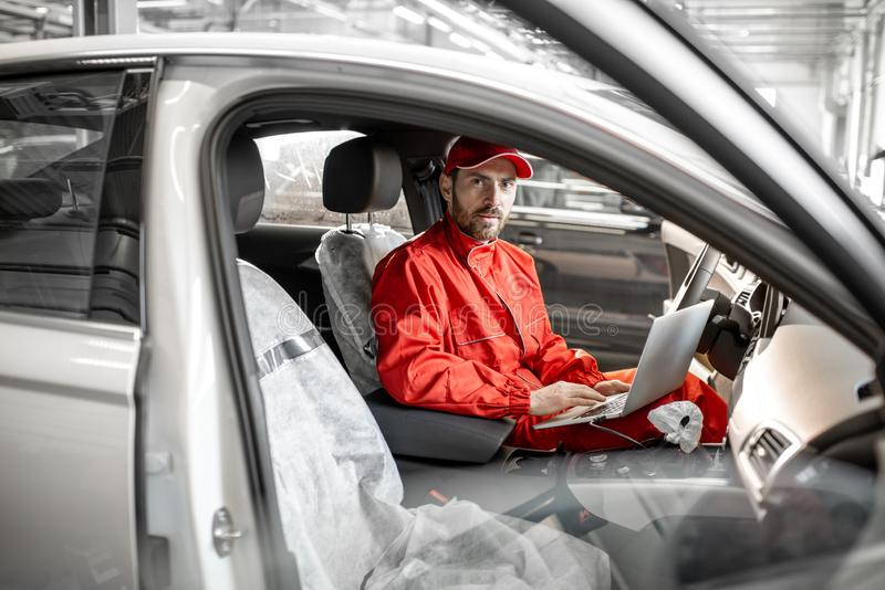 Meccanico che diagnostica automobile con il computer fotografie stock libere da diritti