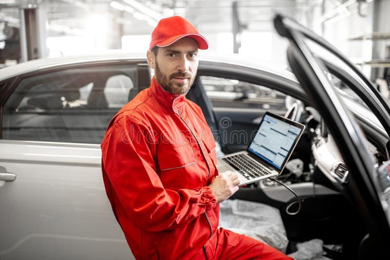 Meccanico che diagnostica automobile con il computer immagini stock libere da diritti
