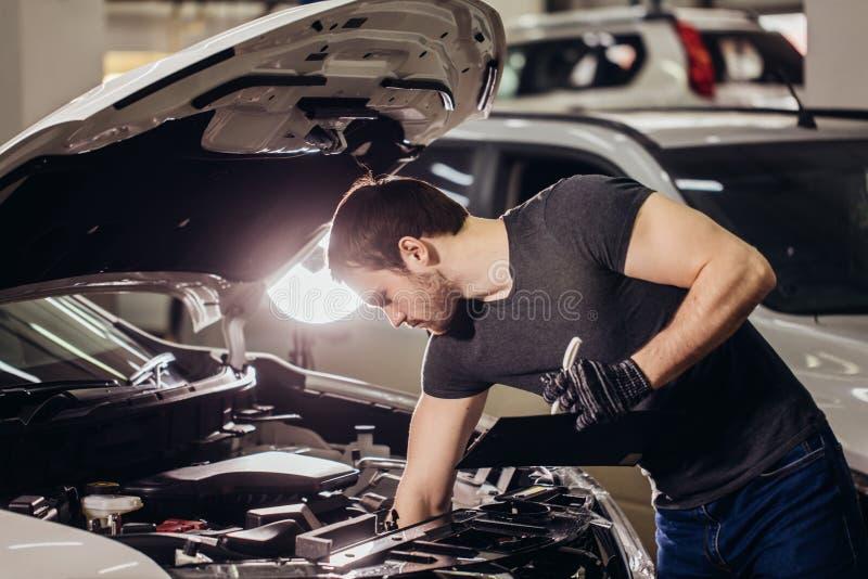 Meccanico che esamina sotto l'automobile del cappuccio e che scrive le note al garage fotografia stock