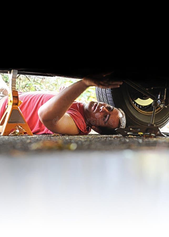 Meccanico che lavora ad un'automobile fotografie stock