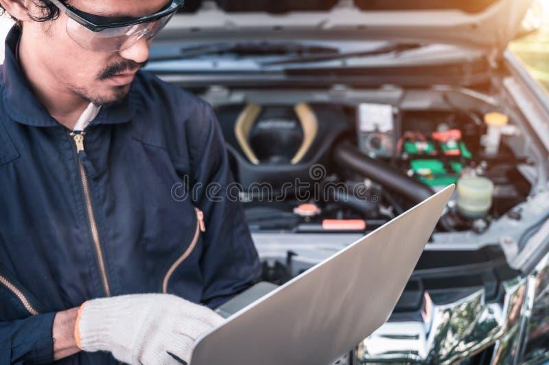 Meccanico che lavora ad un computer collegato ad un motore di automobile all'officina riparazioni fotografie stock