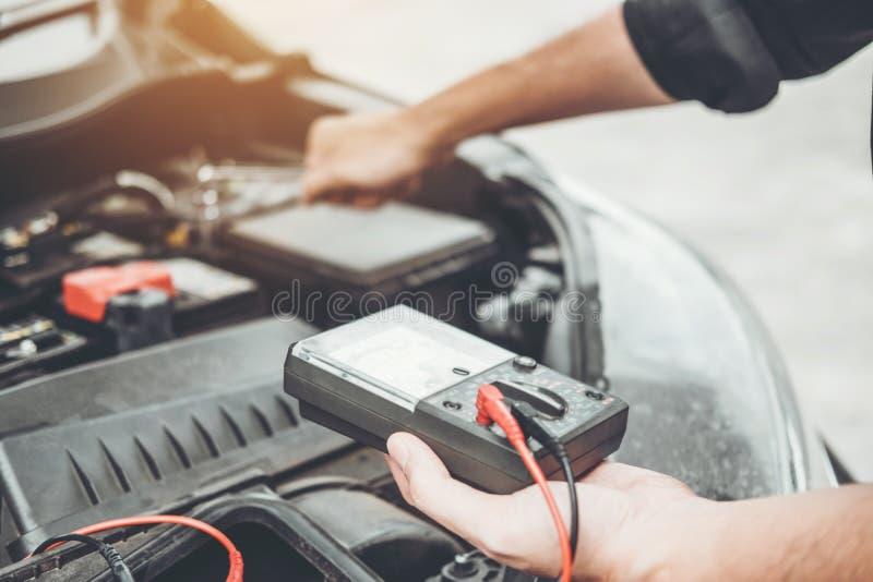 Meccanico che lavora nel tecnico Hands del garage del meccanico di automobile che lavora accumulatore per di automobile in contro fotografia stock libera da diritti