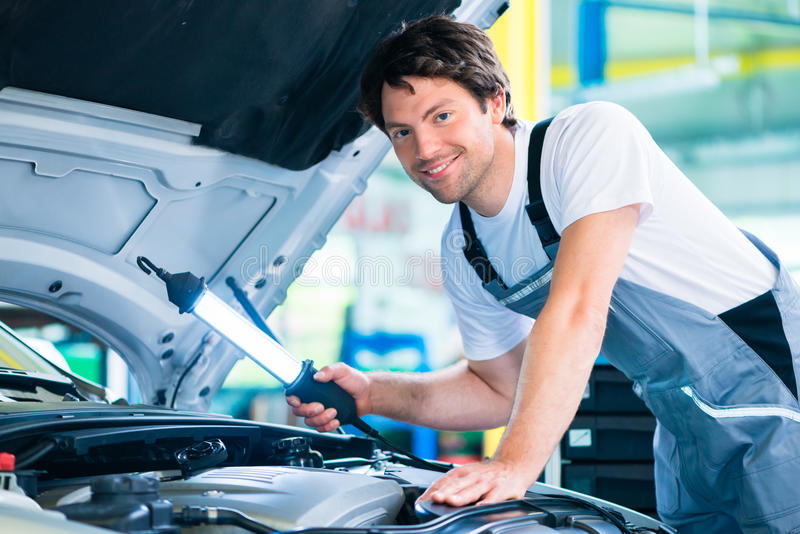 Meccanico che lavora nell'officina di servizio dell'automobile fotografia stock