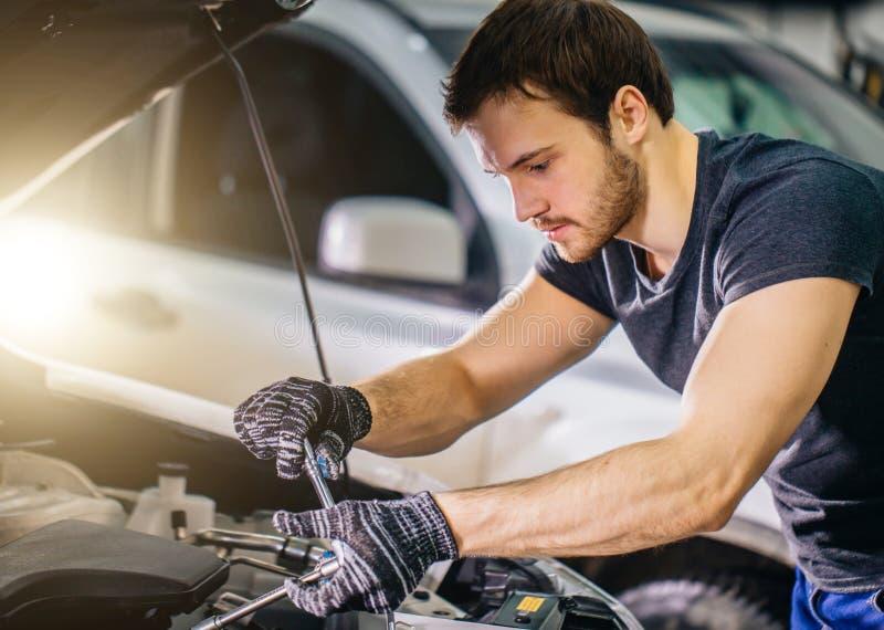 Meccanico che lavora sotto il cappuccio dell'automobile nel garage di riparazione fotografia stock libera da diritti