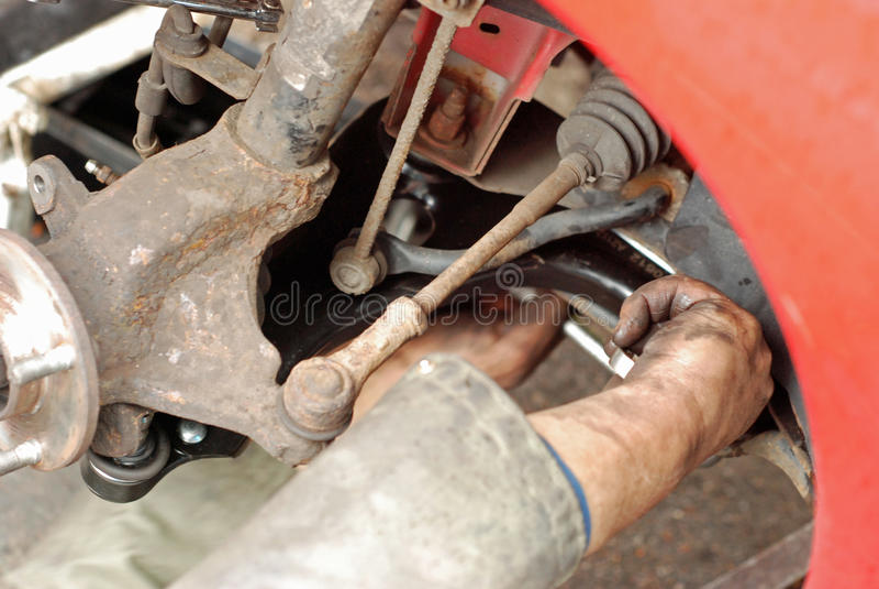 Meccanico che misura il nuovo braccio di sospensione. fotografia stock