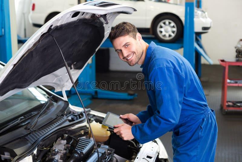 Meccanico che per mezzo della compressa per riparare automobile immagine stock libera da diritti
