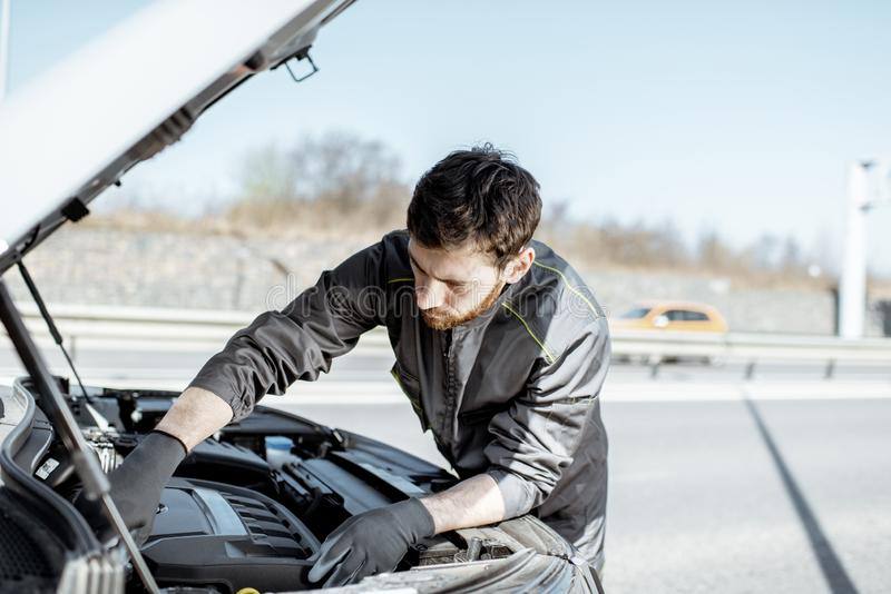 Meccanico che ripara automobile all'aperto fotografia stock libera da diritti