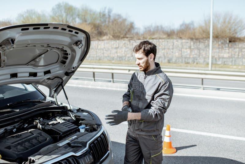 Meccanico che ripara automobile all'aperto immagine stock