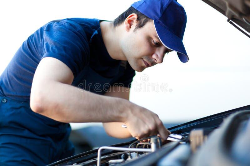 Meccanico che ripara un motore di automobile fotografia stock