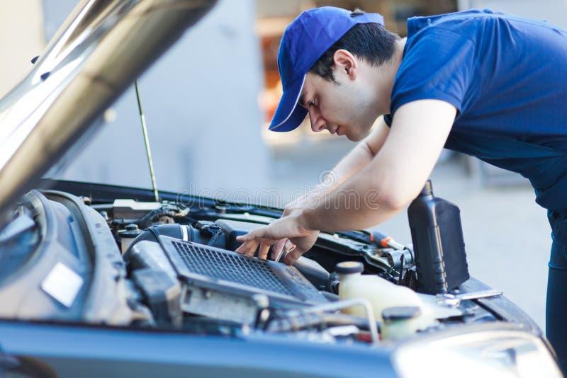 Meccanico che ripara un motore di automobile fotografie stock