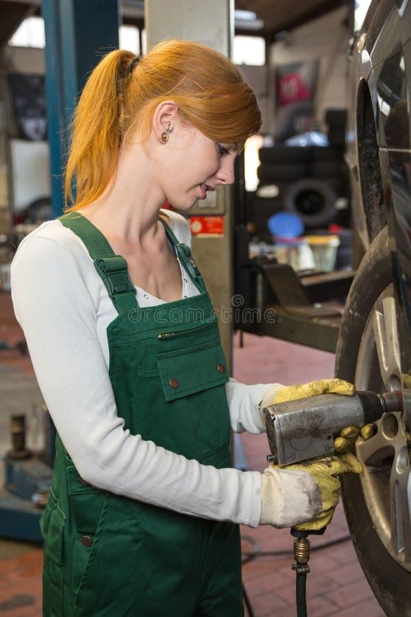 Meccanico che sostituisce la gomma o la ruota su un'automobile in garage o in officina immagini stock libere da diritti