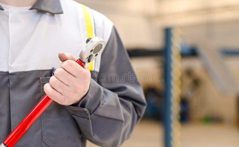 Meccanico con la chiave dinamometrica. immagini stock