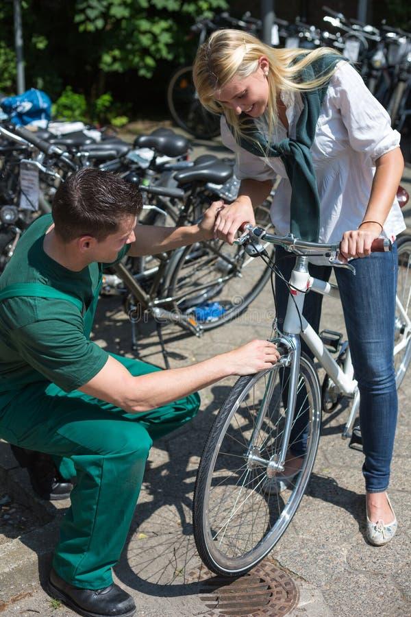 Meccanico della bicicletta nel negozio della bici che consulta un cliente fotografia stock
