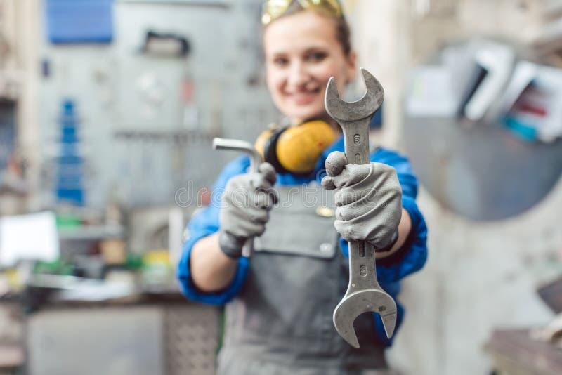 Meccanico della donna che mostra gli strumenti alla macchina fotografica immagine stock