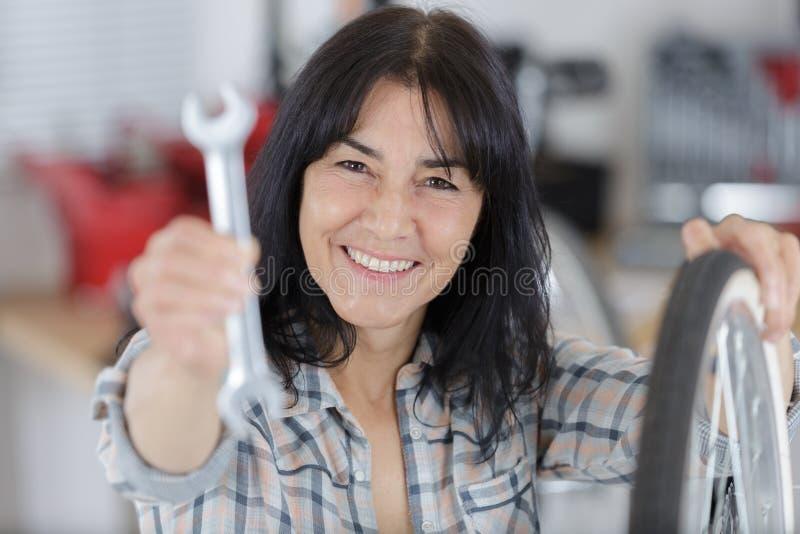 Meccanico della donna che posa con le chiavi ed i pneumatici fotografia stock