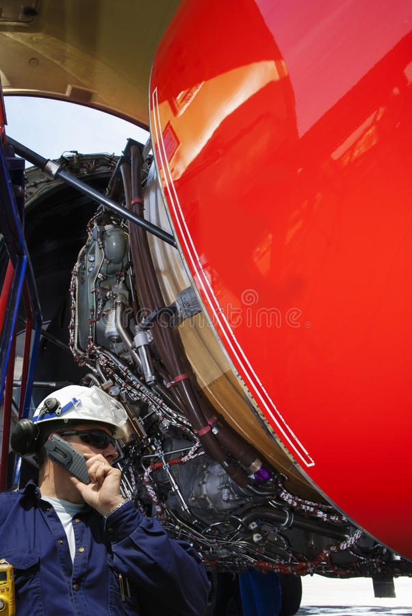 Meccanico di aeroplano che ispeziona il motore a propulsione immagine stock