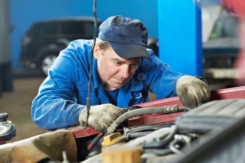 Meccanico di automobile che diagnostica problema automatico del motore fotografie stock