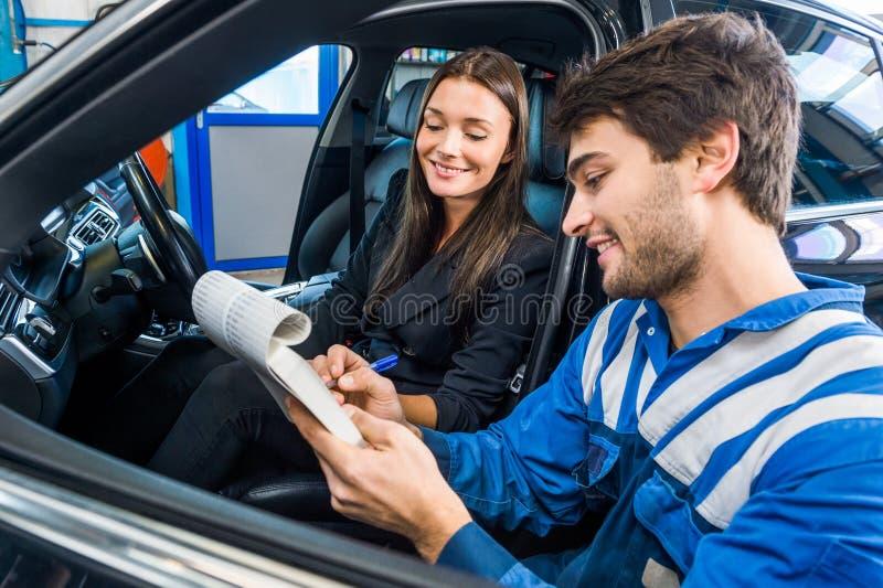 Meccanico di automobile With Customer Going attraverso la lista di controllo di manutenzione fotografia stock
