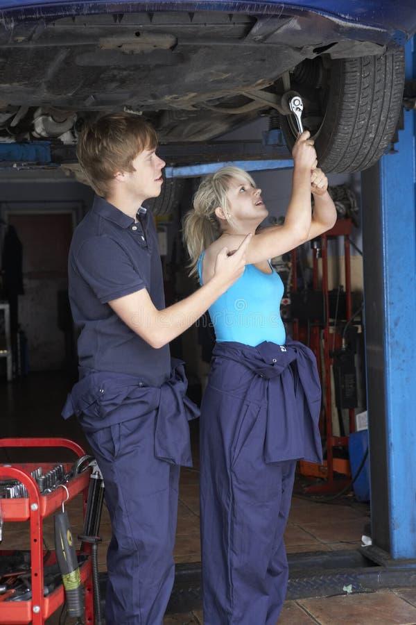 Meccanico ed apprendista che lavorano all'automobile fotografia stock libera da diritti