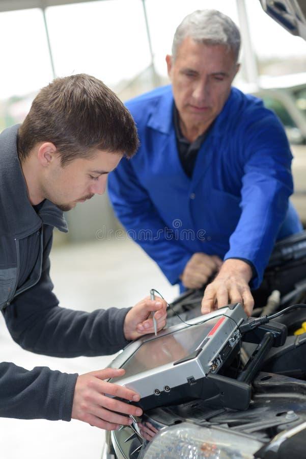 Meccanico ed apprendista che lavorano all'automobile con il computer immagine stock