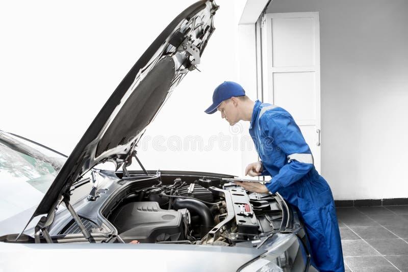 Meccanico europeo che esamina un'automobile con la compressa fotografia stock libera da diritti