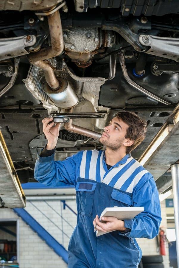 Meccanico Examining Exhaust System dell'automobile con la torcia elettrica fotografie stock