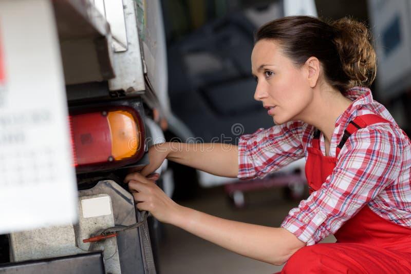 Meccanico femminile che ispeziona veicolo immagine stock libera da diritti
