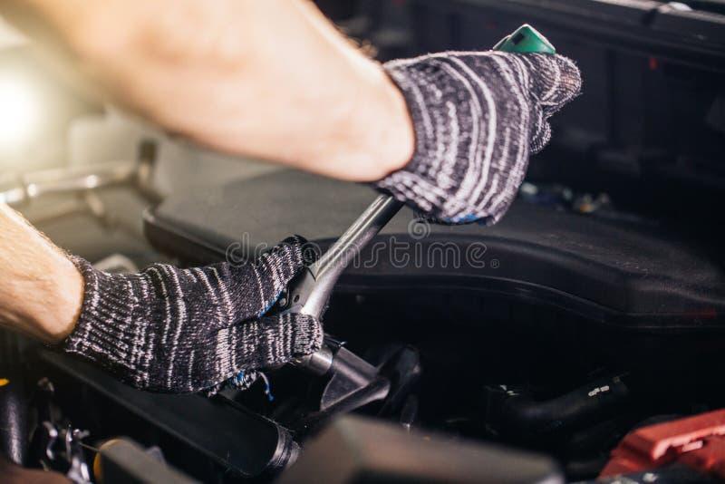 Meccanico la sua officina riparazioni che sta automobile vicina Motore del primo piano immagine stock