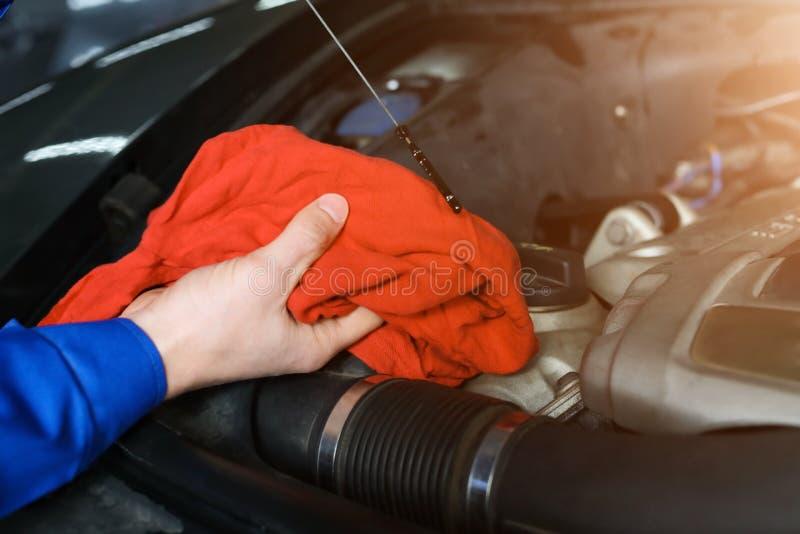 Meccanico maschio che controlla il livello di olio per motori nel centro di servizio dell'automobile fotografie stock