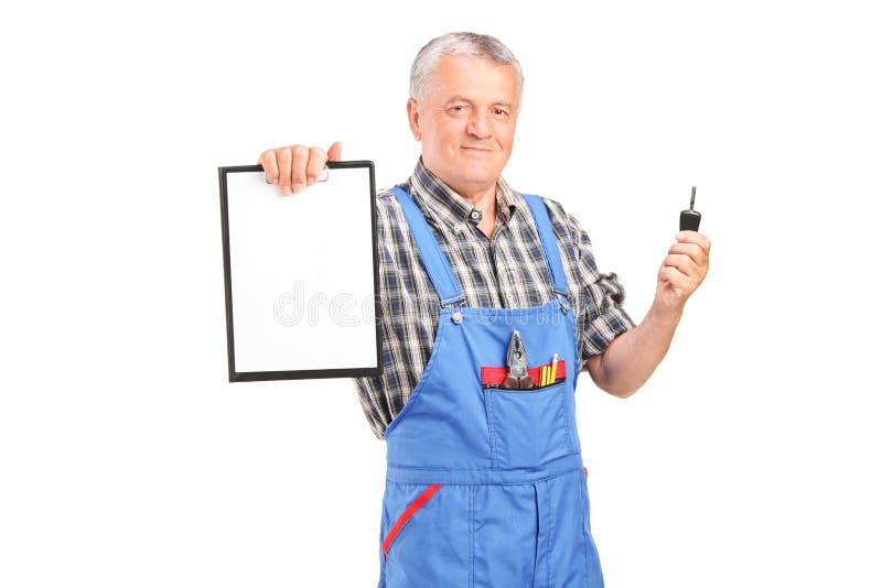 Meccanico maturo che tiene una chiave e una lavagna per appunti dell'automobile fotografie stock