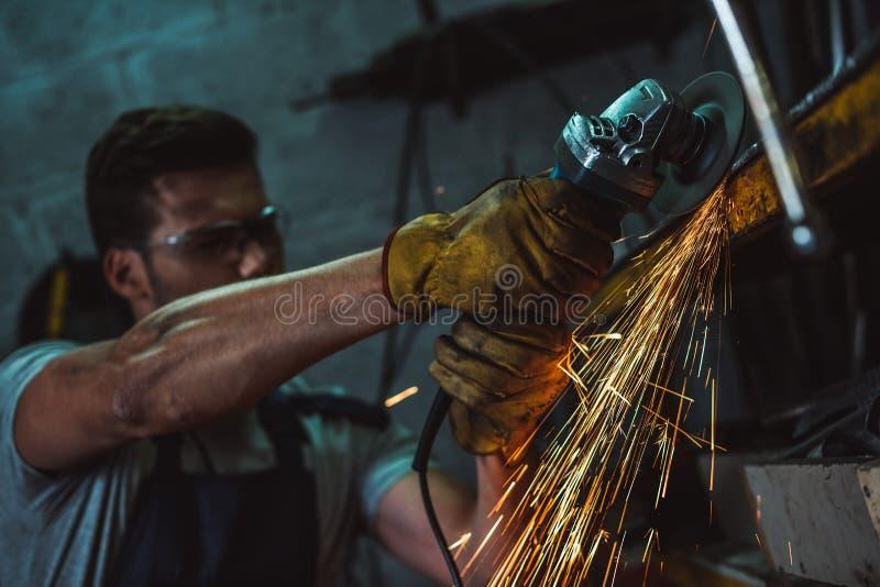 meccanico in occhiali di protezione che lavorano con la sega circolare fotografia stock