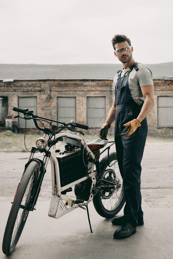 meccanico in occhiali di protezione che riparano l'esterno diritto del motociclo d'annata fotografia stock libera da diritti