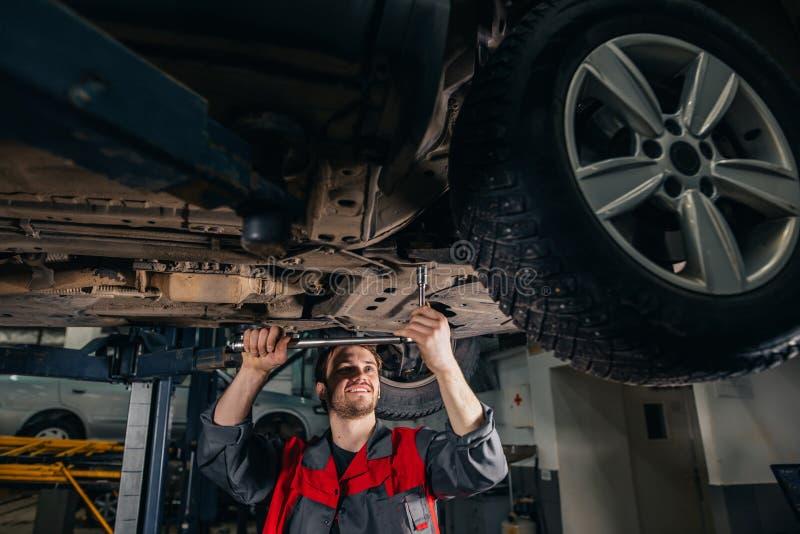 Meccanico sotto l'automobile nella gomma examing del garage e nello stato tecnico immagine stock libera da diritti