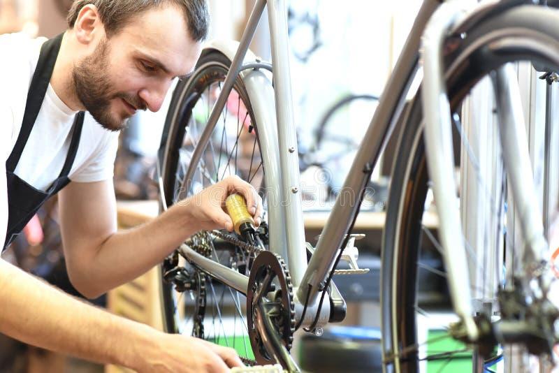 Meccanico in un'officina riparazioni della bicicletta che lubrifica la catena di una bici fotografie stock libere da diritti