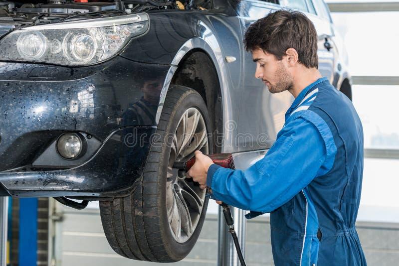 Meccanico Using Pneumatic Wrench per riparare la gomma di automobile fotografie stock