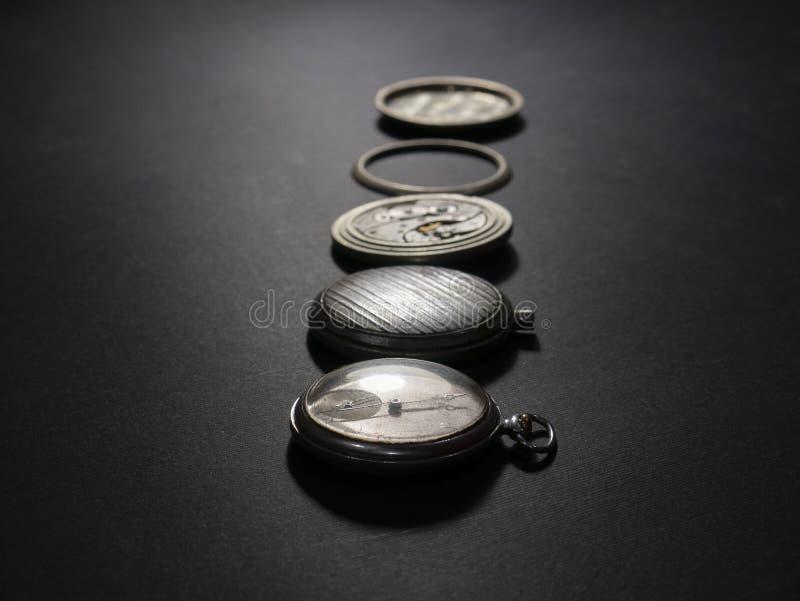 Meccanismi degli orologi e delle loro parti su un fondo nero immagine stock libera da diritti