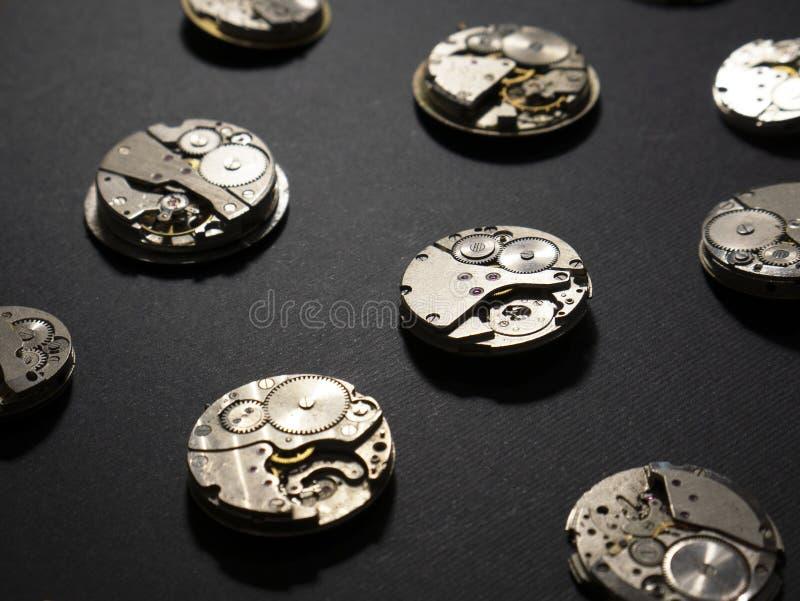 Meccanismi degli orologi e delle loro parti su un fondo nero fotografia stock libera da diritti