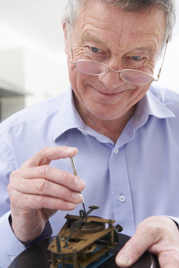 Meccanismo dell'orologio di riparazione dell'uomo senior fotografia stock
