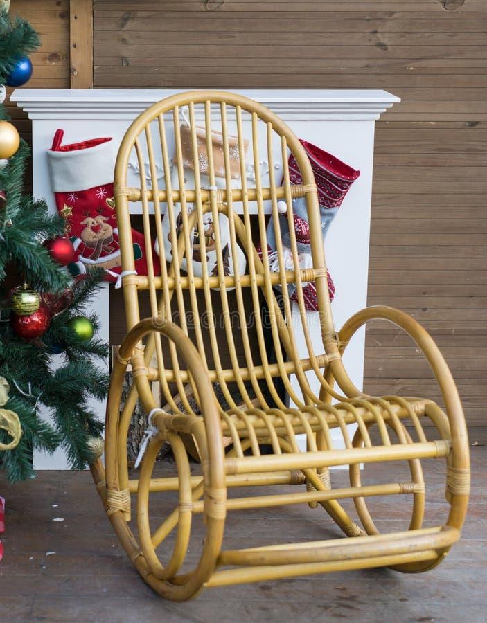 Mecedora al lado de la chimenea con el árbol de navidad fotografía de archivo libre de regalías
